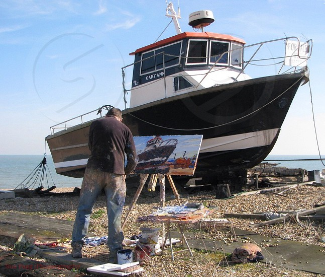 man in black long sleeve shirt and blue denim jeans painting a ship in front of him photo