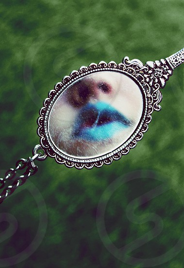 woman with teal lipstick on mirror reflection photo