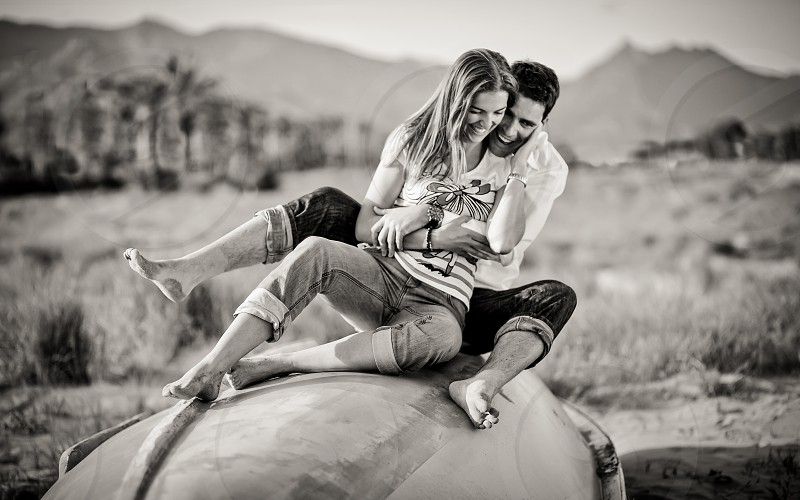 man and woman sitting on rock in grayscale photography photo
