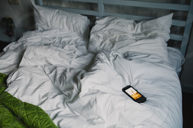 black smartphone on bed photo