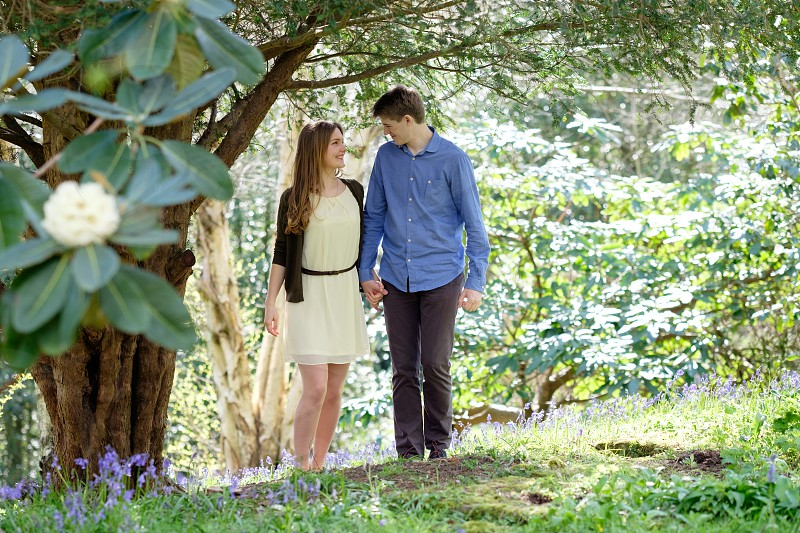 Couple walking in the woods holding hands smiling at each other in the spring  with purple blue bell flowers and yellow flowering tree in the foreground she is wearing a yellow dress and brown cardigan and he is wearing a blue shirt and great trousers. The photo is taken in a landscape composition with copy space around the couple. photo