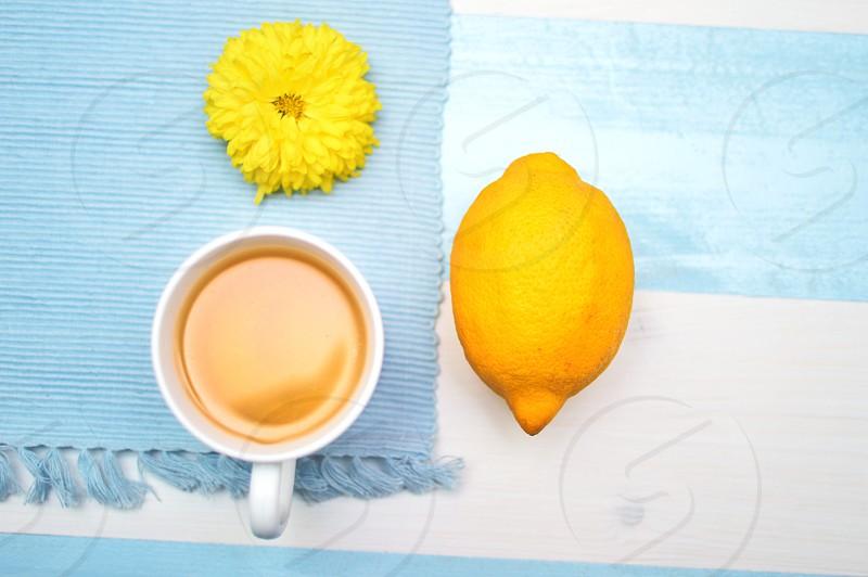 yellow flower and lemon near white ceramic mug with yellow liquid photo