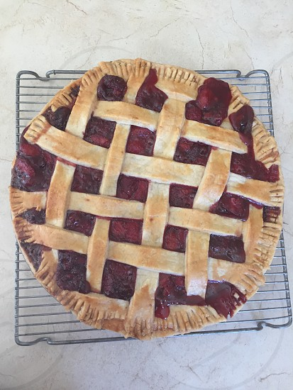 Home made strawberry pie with lattice top crust on cooling rack  photo