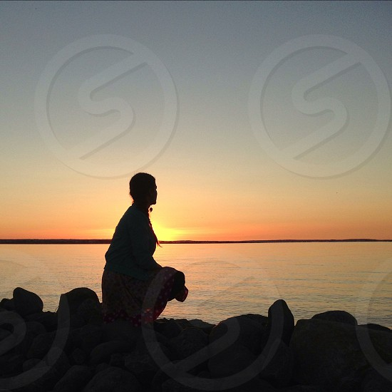 woman sitting on a shore rock in sunset view photo