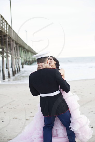bride and groom hugging and laughing on the shore in tilt shift lens photo