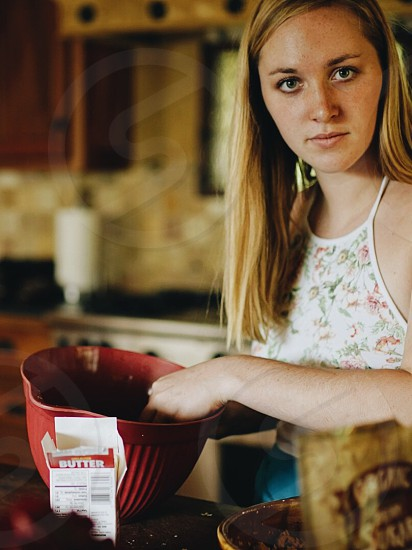 woman in white pink and green floral halter neck top holding red plastic container photo
