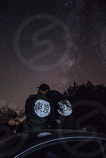 2 person wearing kanji character printed black jacket beside car photo
