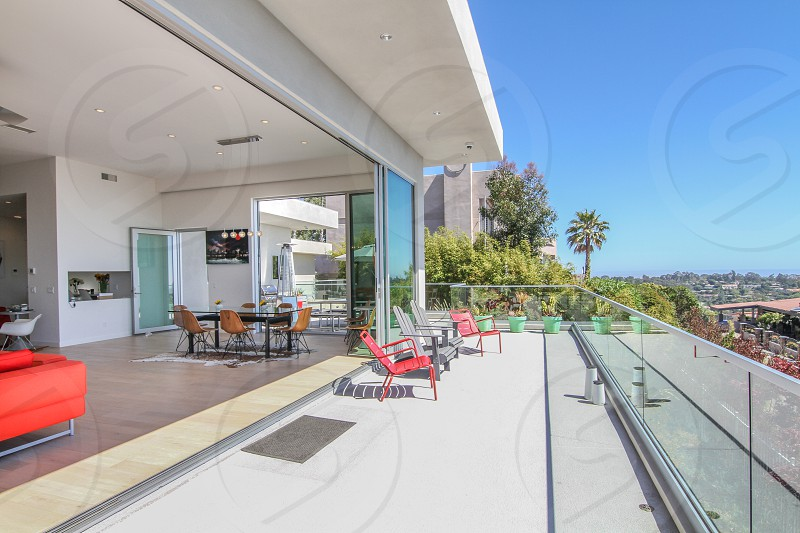 Interior/exterior shot of a balcony with sliding doors that completely open up  photo