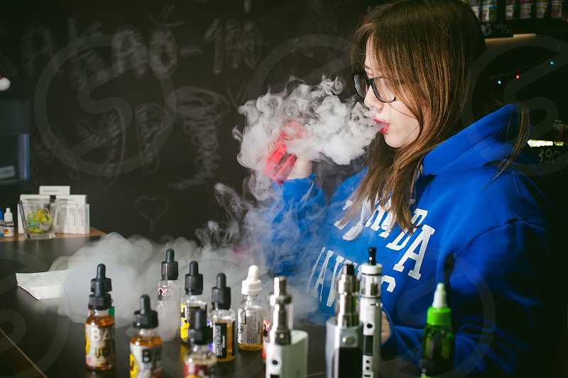 young Cute woman the seller in vape shop shop smoking electronic cigarette  vaping and releases a cloud of vapor photo