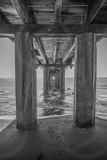 Ocean pier under Black and white sand water tunnel man made wood looking into the distance landscape view underneath waves we dock hawaii kauai dark  photo
