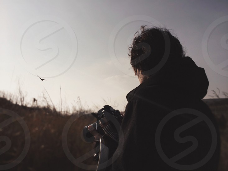 man in black hoodie holding camera standing on brown tall grasses with bird in flight at distance photo