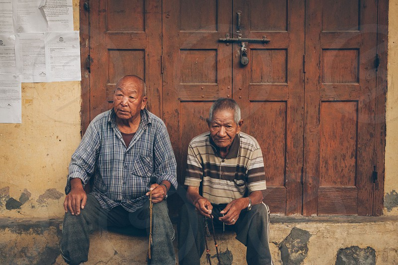 two man sitting infront of a brown wooden door photo