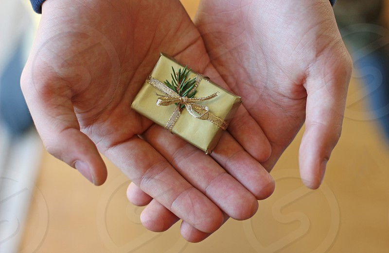 large man's hands holding a very small gold colored gift close-up top view photo