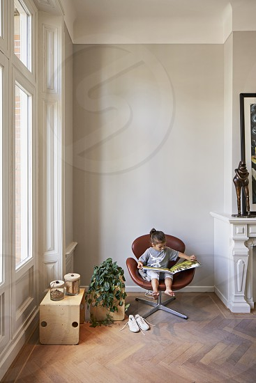 A boy sits on a leather chair and reads a book. photo