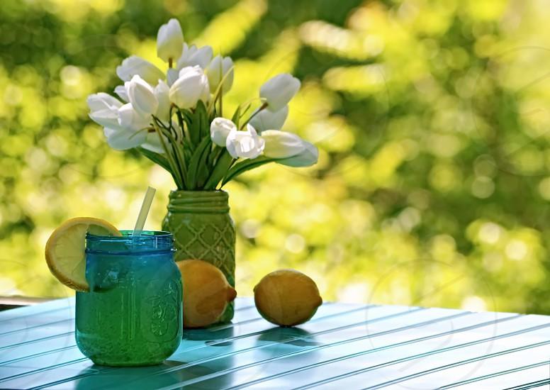 Lemons and lemonade with a vase of white tulips. Mason jars for beverage and vase. photo