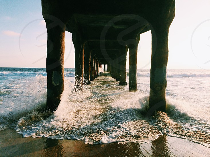 waves breaking on the columns of a dock in the beach photo