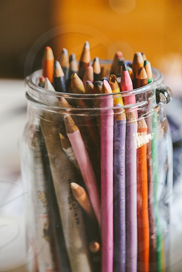 Colorful pens in a glass jar photo