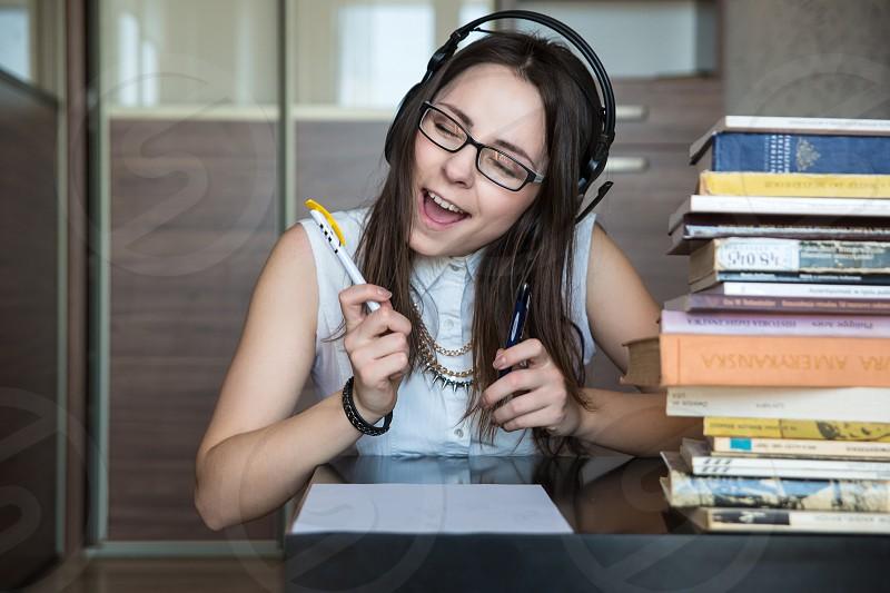 woman in black framed eyeglasses using headphones holding pen on table near stacked books photo