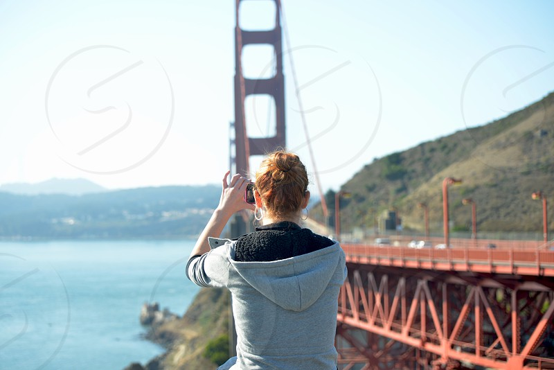 woman taking picture of golden gate bridge photo
