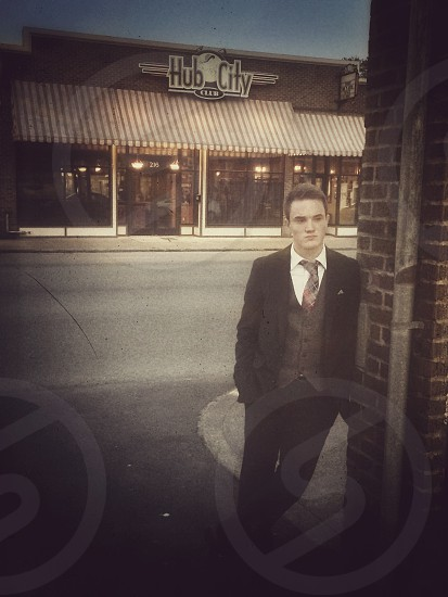 man in black formal suit leaning on brown concrete bricked wall outdoor photo