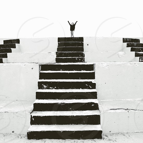 Woman at the top of flight of stairs arms raised.  photo