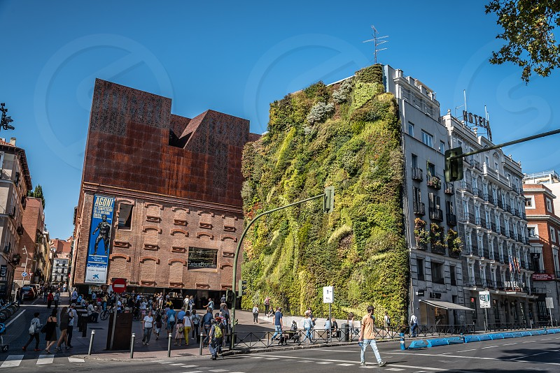 Outdoors view of CaixaForum Madrid is a museum and cultural center in Paseo del Prado  sponsored by La Caixa Bank. It was constructed by the Swiss architects Herzog & de Meuron with oxidized cast-iron facade. On the house next to it there is a green wall photo