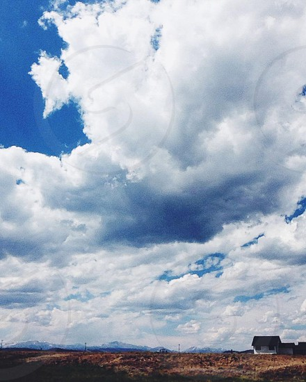 house under blue sky and white clouds photo