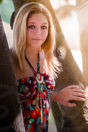 woman in maroon red blue white floral halter top standing between brown trees photo