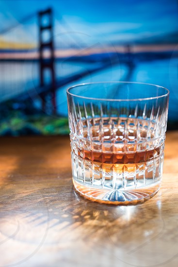 whisky glass with whisky in focus over wooden table golden gate bridge landmark sunset in background out of focus photo
