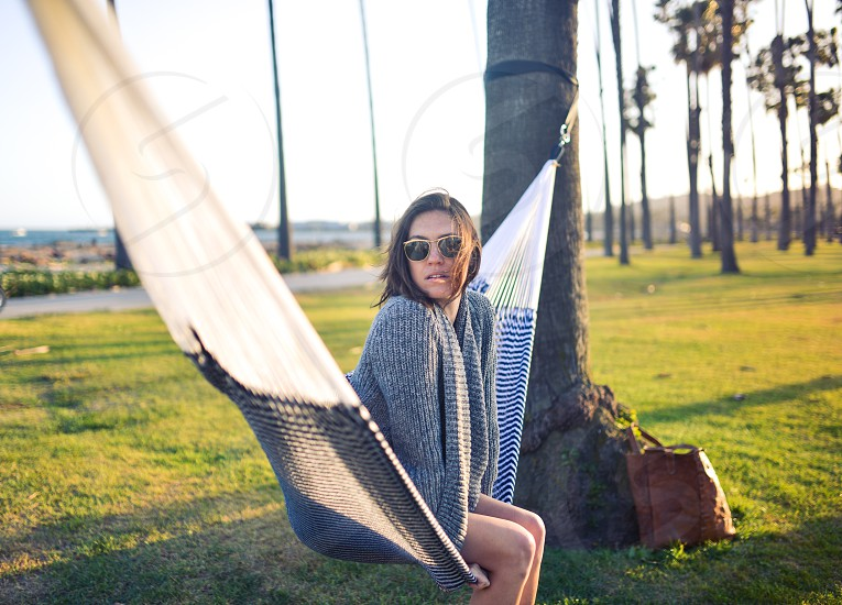 Woman looking at camera sitting in a hammock in a park photo