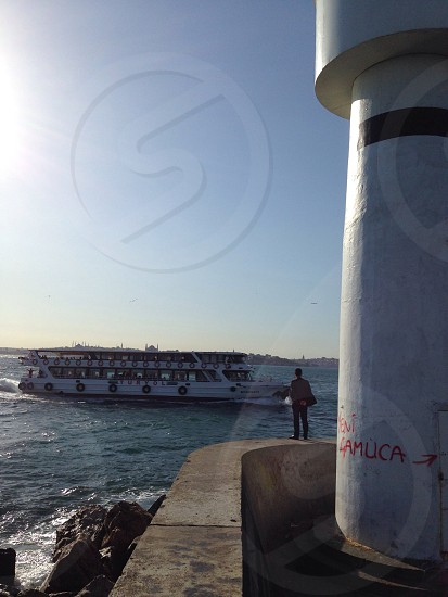 A man watches a ferry pass on the Bosphorus in Istanbul Turkey photo