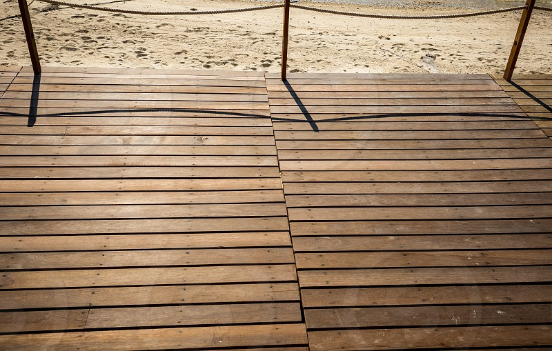 Seaside front wooden deck facing late afternoon sun. Horizontal deck lines next to sandy beach photo
