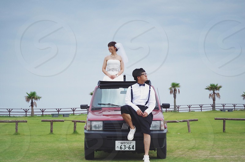 pre nup photo of married couple standing and sitting on red fiat sedan surrounded by green grass field during daytime photo