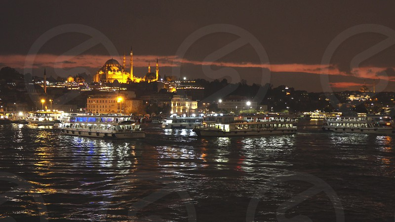 Night town sityscape to Golden Horn with large number of tourist ships and view to Suleymaniye Mosque on a background of twilight sky Istanbul Turkey. 4K UHD video 3840 2160p. photo