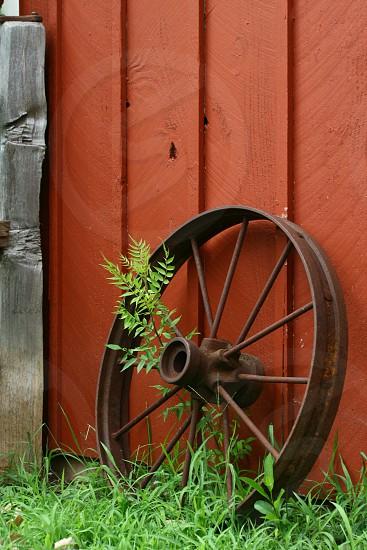 brown metal wheel rim against red painted wood photo