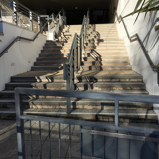 beige tiled stairs with gray metal handrails photo