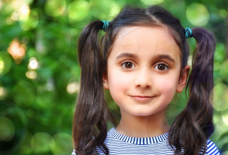girl with black hair tied in pigtail smiling photo