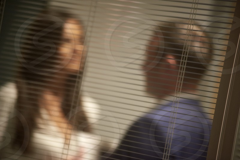 A man and a woman in the office behind open blinds having a discussion possibly an affair  photo