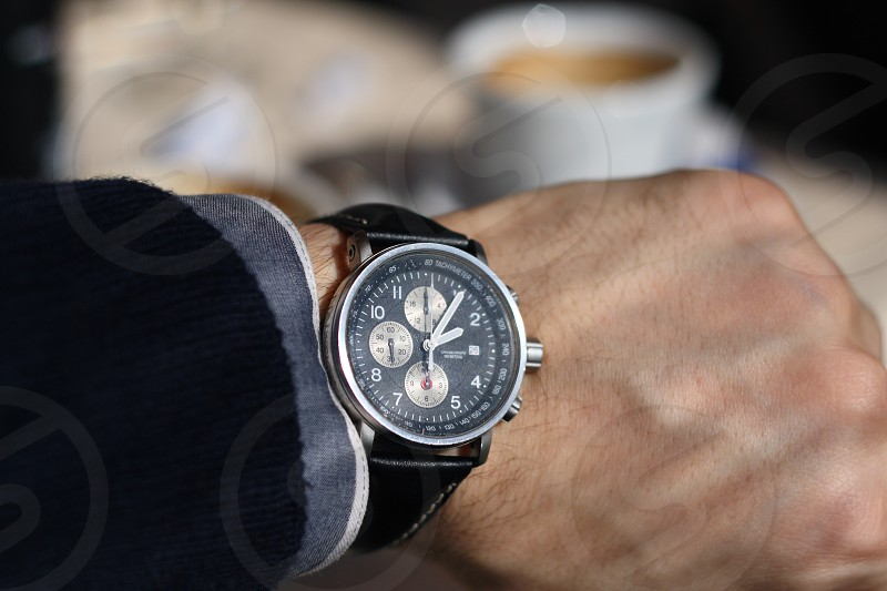 Mans hand wearing wrist watch with coffee in the back photo