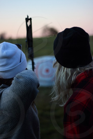 woman shooting a bow and arrow at a target photo