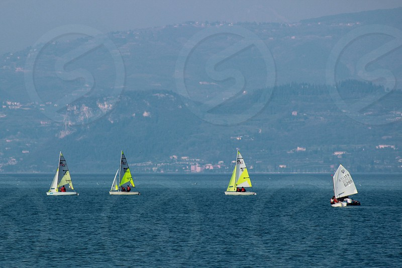 yellow and white sailboats on water with mountain in background during daytime photo