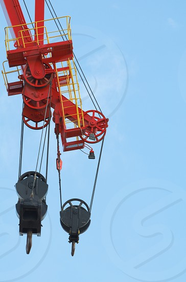 Red and Black Colored Heavy Crane Pulleys Against Blue Sky photo