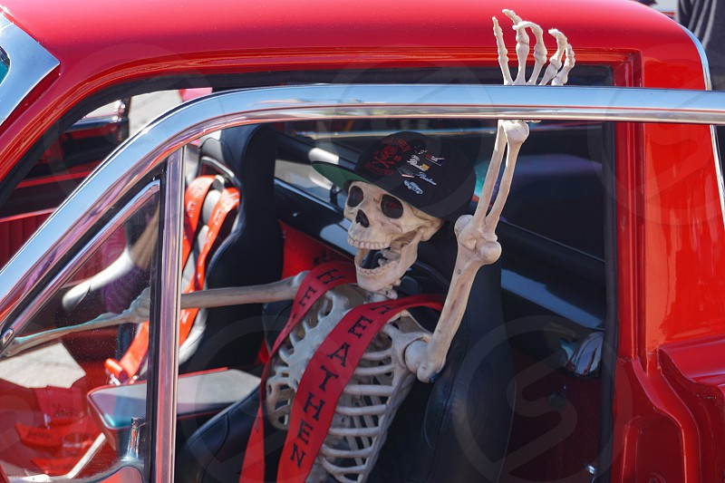 Tehachapi California USA-October 14 2018: Skeleton driver in sporty red pickup truck promises a scary ride at fall apple festival car show. photo