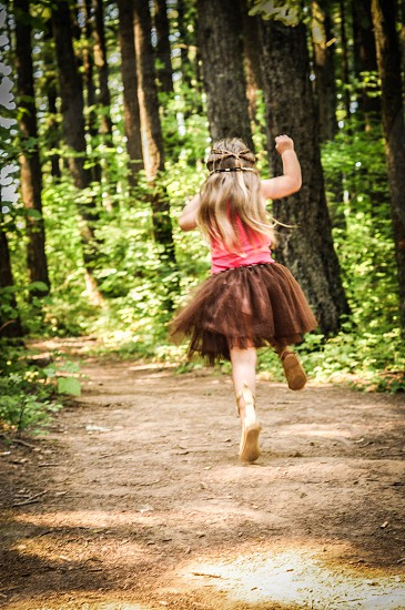 girl in pink tank top and brown tutu skipping down dirt path in forest photo