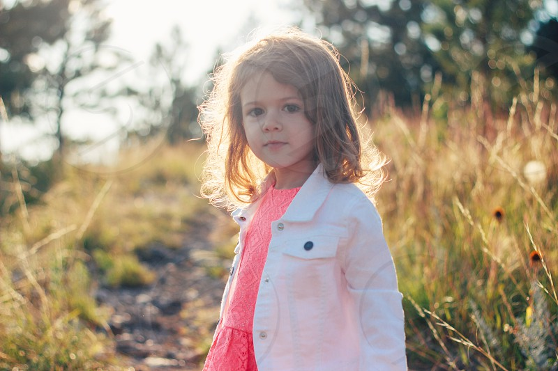 girl in white jacket standing in a field photo