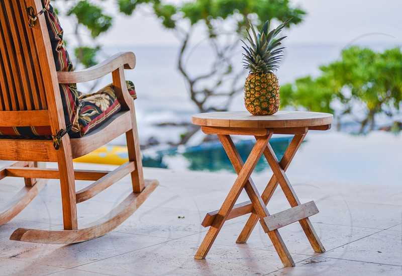 poolside furniture with pineapple at tropical locale photo