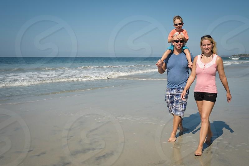 Family of 3 enjoying walk on the beach Riviera Nayarit Mexico photo