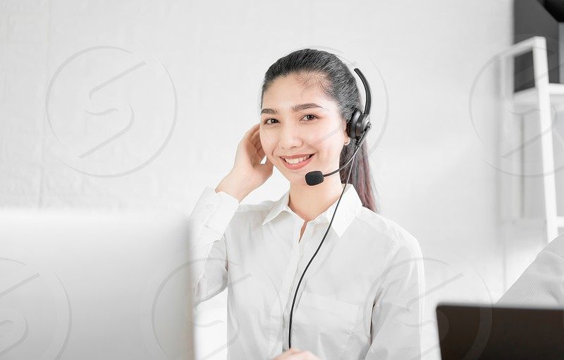 Beautiful Asian woman consultant wearing microphone headset of customer support phone operator at workplace. photo