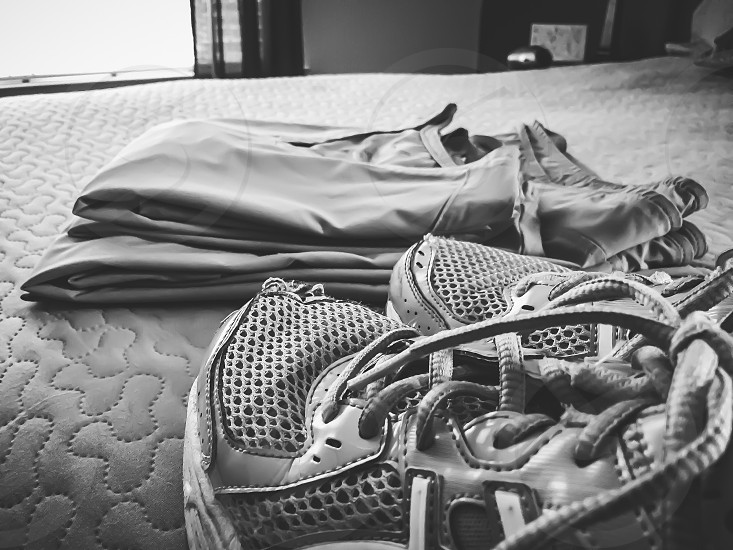 Registered nurse uniform. Scrubs folded neatly on bed with a comfortable pair of waking sneakers / shoes. photo