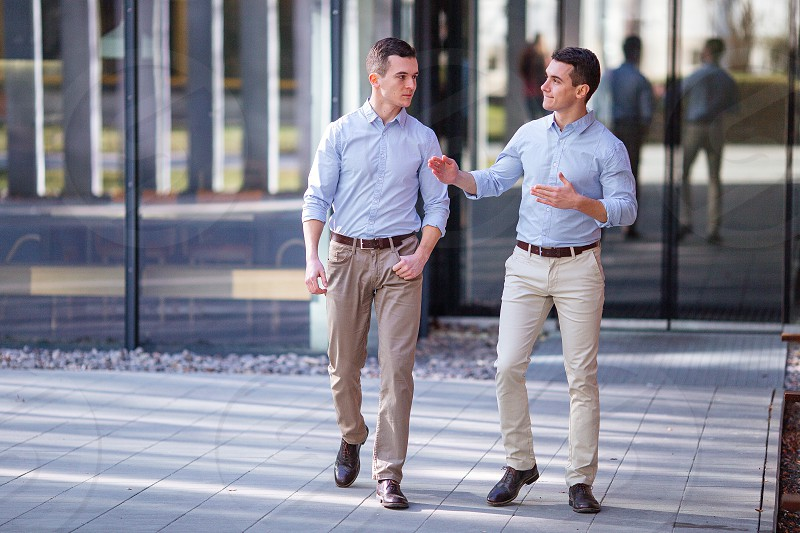Two businessman walking and talking about business with street city blur background photo